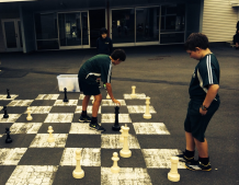 Ari Eady and Ty Cherry take the opportunity to play outdoor chess. Ari is about to take Ty's queen while Ty ponders his next move.
